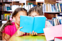 Two girls reading a book. In a library Royalty Free Stock Photos