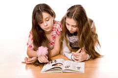 Two girls reading book on the floor on white Royalty Free Stock Photos