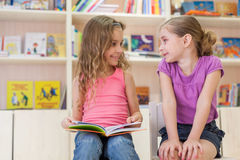 Two girls reading a book in the library and laugh. Focus on right girl Stock Image
