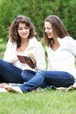 Two girls reading book outdoors Royalty Free Stock Photo