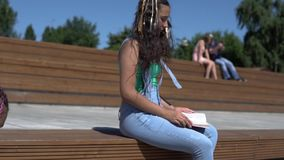Two girls are reading a book sitting on a park bench. slow motion. Two beautiful girls are reading a book sitting on a park bench. slow motion stock footage