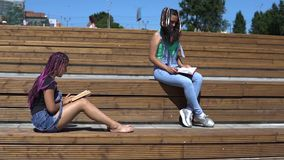 Two girls are reading a book sitting on a wooden bench in the park in sunny weather. slow motion. Two beautiful girls read a book sitting on a wooden bench in a stock video footage