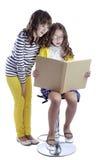 Two girls reading book. On white background Stock Photos
