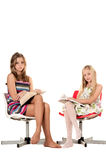 Two girls reading books. Sitting in a studio Royalty Free Stock Photography