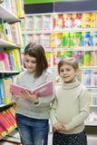 Two girls reading books at store. Portrait of girls of 8 and 6 years in shop choosing books stock image
