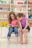 Two girls reading a fascinating book. In the library stock photo