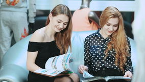 Two Girls reading fashion Magazine. Young girls looking trough fashion magazines sitting on sofa in shop stock video