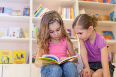 Two girls are reading an interesting book. In the library stock images