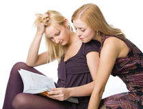Two girls reading magazine Stock Images