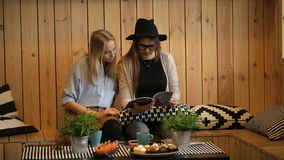 Two girls reading magazine and smilling. Friendship and happiness concept - two girls reading magazine in cafe stock footage