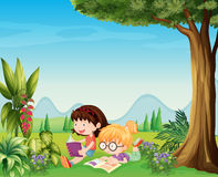 Two girls reading near the plants Stock Images