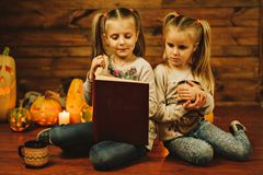 Two girls preparing for the holiday. Night, candles, pumpkin, tales. Two girls are reading an old book. Halloween Stock Images
