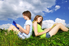 Two girls reading outdoors in summer royalty free stock image