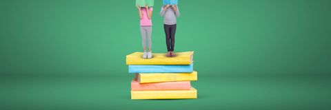 Two girls reading and standing on a pile of books with green background royalty free stock image