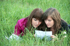 Two girls reading together on grass Stock Photos