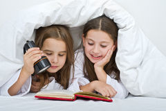 Two girls reading under blanket. With flashlight Royalty Free Stock Photography