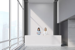 Two girls  at a reception desk Stock Image