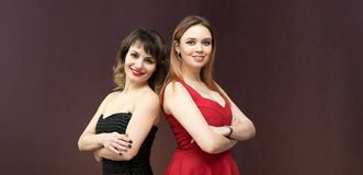 Best friends stand with their backs to each other. Two girls in red and black dress in the apartment on a dark background stock image