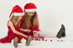 Two girls in a red dress in caps Santa Claus sitting on the floor Stock Photos