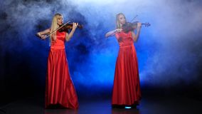 Two girls in a red dress playing the violin. Studio. Smoke. Two gorgeous blonde, professional fiddlers, with long hair, playing the violin professional stock video