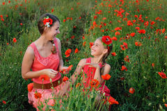 Two girls in red dress on poppy field Royalty Free Stock Photography