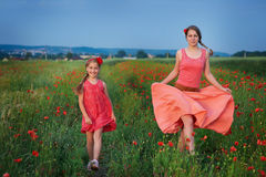 Two girls in red dress walking on poppy field Royalty Free Stock Images