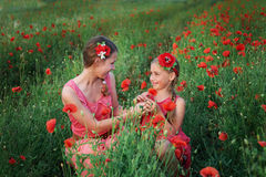 Two girls in red dress walking on poppy field Stock Photo