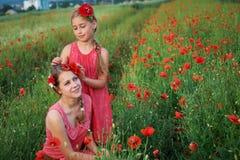 Two girls in red dress walking on poppy field Royalty Free Stock Image