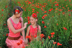 Two girls in a red dress walking on the poppy field in Spring royalty free stock photography