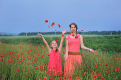 Two girls in a red dress walking on the poppy field in Spring Stock Photos
