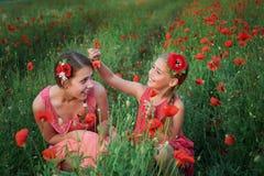 Two girls in red dress walking on poppy field Stock Photography