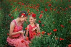 Two girls in red dress walking on poppy field Royalty Free Stock Photo
