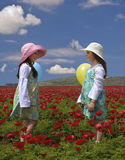 Two girls in a red field. Of Popey Anemon flowers and ballons Stock Image
