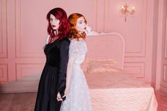 Two beautiful girls with red hair in a beautiful white wedding Victorian dresses. Two girls with red hair in retro dress in the bedroom. Femme fatale in a black Royalty Free Stock Photo