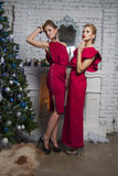 Two Girls in red party dress near new year tree Stock Images