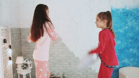 Two girls in red and pink pajamas fighting with pillows. Happy laughing children, fight a pillow at home stock footage