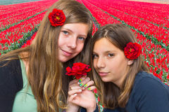 Two girls with red roses in front of tulip field. Two dutch teenage girls with long hair and red roses in front of flower field Stock Photography