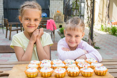 Two girls rejoice freshly baked cupcakes Stock Image