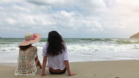 Two girls relaxing on beach in slow motion. Happy young adults in love sitting relaxed in the sand stock video