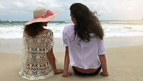 Two girls relaxing on beach in slow motion. Happy young adults in love sitting relaxed in the sand stock video footage
