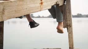 Two girls relaxing by the lake sitting on the wooden pier swing with feet stock video