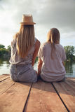 Two Girls Relaxing Near River Royalty Free Stock Photography