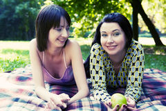 Two girls relaxing in park Stock Photos