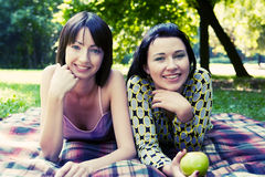 Two girls relaxing in park Stock Images