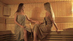 Two girls relaxing in the sauna stock video