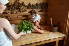 Two girls relaxing in sauna. Two beautiful young women in towels realxing in wooden sauna. ine shot with natural light Stock Image