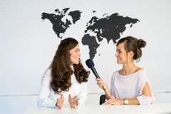 Two girls reporters twins are reporting from a white studio Royalty Free Stock Image