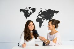 Two girls reporters twins are reporting from a white studio Royalty Free Stock Photo