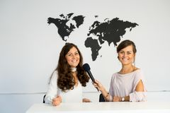 Two girls reporters twins are reporting from a white studio Stock Image