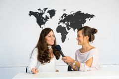 Two girls reporters twins are reporting from a white studio Royalty Free Stock Images